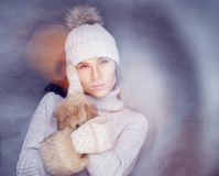 Brunette woman in warm winter pullover. Brunette woman in warm winter pullover,fur gloves posing in fog Royalty Free Stock Images