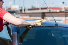 Brunette woman washes her car Royalty Free Stock Image