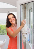 Brunette woman washing windows in house Royalty Free Stock Photos