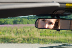 Brunette woman watching on rear-view mirror. Brunette woman sitting in car and watching to rear-view mirror Royalty Free Stock Photo
