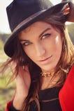 Brunette woman wearing black felt hat with golden. Close-up portrait of pretty brunette woman wearing black felt hat with golden chain necklace. Blurred Stock Photo