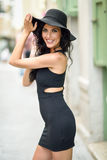 Brunette woman wearing black seductive dress in the street Stock Photography