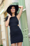 Brunette woman wearing black seductive dress in the street Stock Photos
