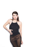 Brunette woman wearing a black top and gold pants on a white background Stock Photos