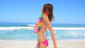 Brunette woman wearing a flower garland. On the beach stock video footage