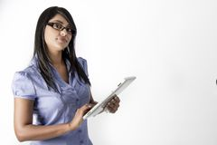 Brunette woman wearing glasses holding a tablet Stock Photos