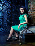 Brunette woman. Wearing a green dress in the room with old walls and furniture Stock Photos