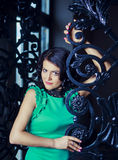 Brunette woman. Wearing a green dress in the room with old walls and furniture Stock Image