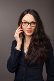 Brunette woman wearing jacket talking on the cell phone Stock Images