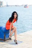 Brunette woman wearing orange short dress in a harbor Stock Photo