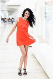 Brunette woman wearing orange short dress in the street Royalty Free Stock Photography