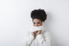 Brunette woman wearing white sweater. Indoors Stock Image