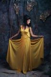 Brunette woman wearing yellow evening dress Royalty Free Stock Photos