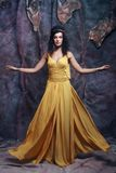 Brunette woman wearing yellow evening dress Royalty Free Stock Images