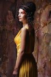 Brunette woman wearing yellow evening dress Stock Image