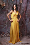 Brunette woman wearing yellow evening dress Stock Images