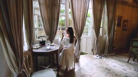 A brunette woman in a white dress sits at a table and drinks water. Vintage interior of the room in the background. / stock video footage