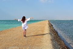 the brunette woman in white dress standing on pier with her hands up against the background of the Dead Sea stock photo