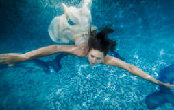Brunette woman in white dress swimming underwater at pool Stock Photo