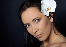 Brunette woman with white orchid over black Royalty Free Stock Image