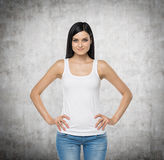 Brunette woman is in a white tank top and blue denims. Royalty Free Stock Photo