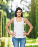 Brunette woman is in a white tank top and blue denims. Royalty Free Stock Photography