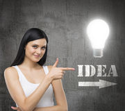 Brunette woman is in a white tank top. She points out the lightbulb and the word IDEA with the arrow. Royalty Free Stock Image