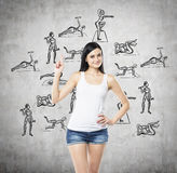 A brunette woman who is offering an affordable way to be healthy and practice physical culture and activities. Concrete background Stock Photography