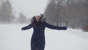 Brunette woman in a winter park. Walks in the open air. Brunette woman in a winter park, slow motion stock footage