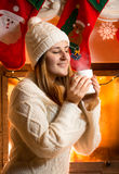 Brunette woman in woolen sweater holding vaporing cup at firepla Stock Images