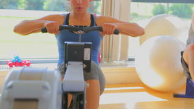 Brunette woman working out on row machine Stock Photos