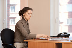 Brunette woman works  in the office, makes notes Royalty Free Stock Photography