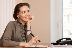 Brunette woman works  in the office, makes notes Royalty Free Stock Photo