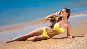 Brunette woman yellow bikini sea Stock Photography