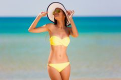 Brunette woman yellow bikini sea Stock Images