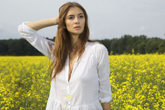Brunette woman in a yellow flowers field Royalty Free Stock Photo