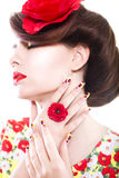 Brunette woman in yellow and red dress with poppy flower in her hair, poppy ring and creative nails, closed eyes Stock Photo