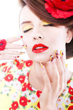 Brunette woman in yellow and red dress with poppy flower in her hair, poppy ring and creative nails, closed eyes Stock Photos