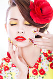 Brunette woman in yellow and red dress with poppy flower in her hair, poppy ring and creative nails, closed eyes Royalty Free Stock Photo