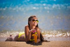 Brunette woman yellow swimsuit drink cocktail Stock Images