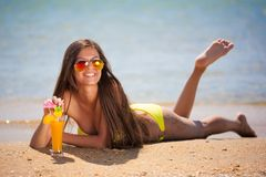 Brunette woman yellow swimsuit drink cocktail Royalty Free Stock Image
