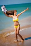 Brunette woman yellow swimsuit jump Royalty Free Stock Photos