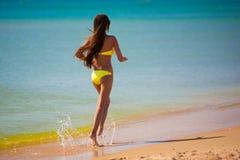 Brunette woman yellow swimsuit sea Stock Photo