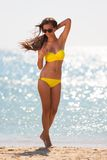 Brunette woman yellow swimsuit sea Royalty Free Stock Images