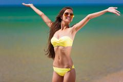 Brunette woman yellow swimsuit sea Stock Images