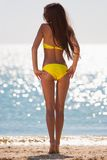 Brunette woman yellow swimsuit sea Stock Photos