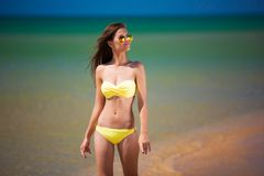 Brunette woman yellow swimsuit sea Royalty Free Stock Photos