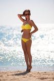 Brunette woman yellow swimsuit sea Stock Photography