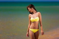 Brunette woman yellow swimsuit sea Stock Image