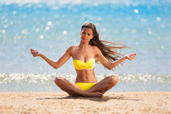 Brunette woman yellow swimsuit yoga. Beautiful brunette woman yellow swimsuit blue sea yoga meditation Stock Images